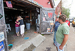 "APALACHICOLA, FL - OCTOBER 09: Janes Frost, right, the owner of the Apachicola Ice Company bar watches as his fiancée Erin Sue Rodgers, left hugs her mother Mary Lynn Rodgers as they depart from getting the bar ready for the arrival of Hurricane Michael in Apalachicola on October 9, 2018 in Apalachicola, Florida. ""This ain't our first rodeo"" Frost said of the bar's storm surge preparation.  (Photo by Mark Wallheiser/Getty Images)"