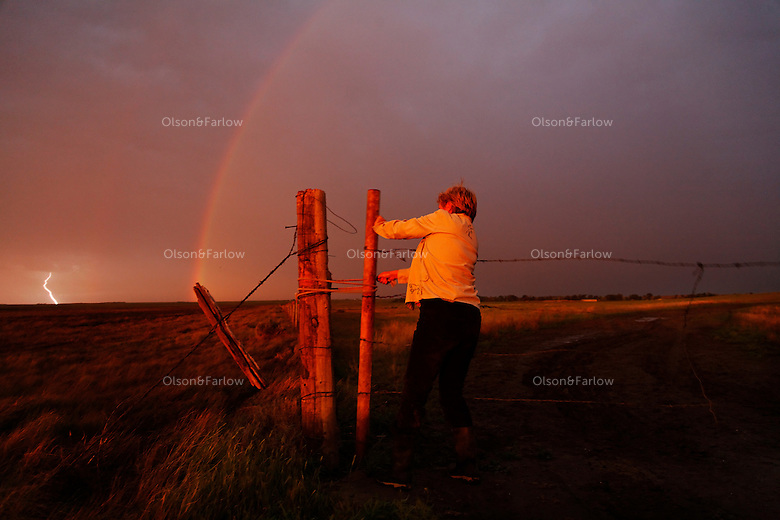 Lightning strikes and a rainbow appears in the North Dakota plains where Karen Sussman closes a gate to keep her mustang herd enclosed. She is president of International Society for the Protection of Mustangs and Burros.