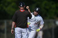 Edgewood Eagles Jacob Yellovich (33) fist bumps head coach Al Brisack while running the bases after hitting a home run during the first game of a doubleheader against the UW-Stout Blue Devils on March 16, 2015 at Lee County Player Development Complex in Fort Myers, Florida.  UW-Stout defeated Edgewood 6-1.  (Mike Janes/Four Seam Images)