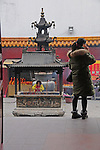 rear of a woman on cell phone standing before the ornate, pagoda roofed incense burner at which another woman makes an offering, at Buddhist temple, Guilin, China