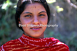 A woman wearing a red sari with a bindi on her forehead in Tehri Garwhal, India.