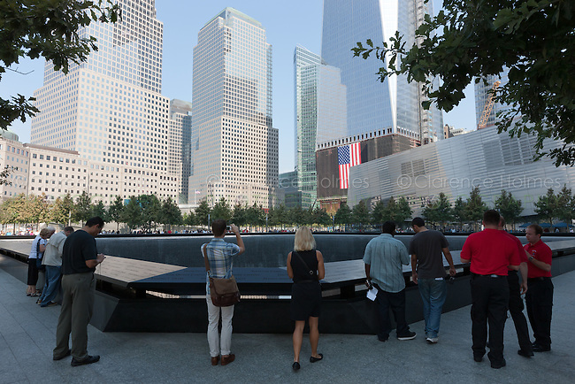 Visitors stand by the South Pool at the National 9/11 Memorial in New York City.