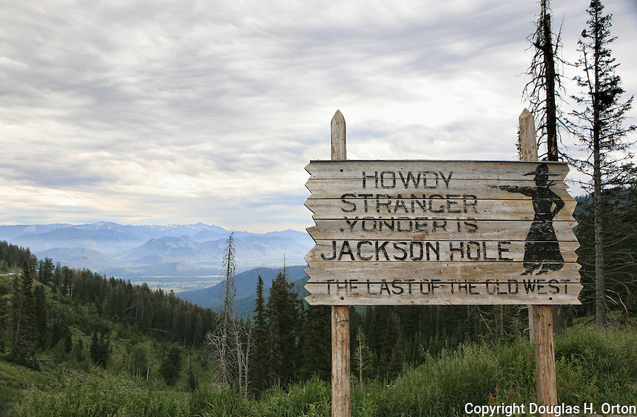 Jackson Hole Sign at Teton Pass.  Teton Pass view to east down to Jackson Hole.  Teton Pass is a steep, two lane scenic drive between Jackson Wyoming and Victor, Idaho in the Teton Valley.