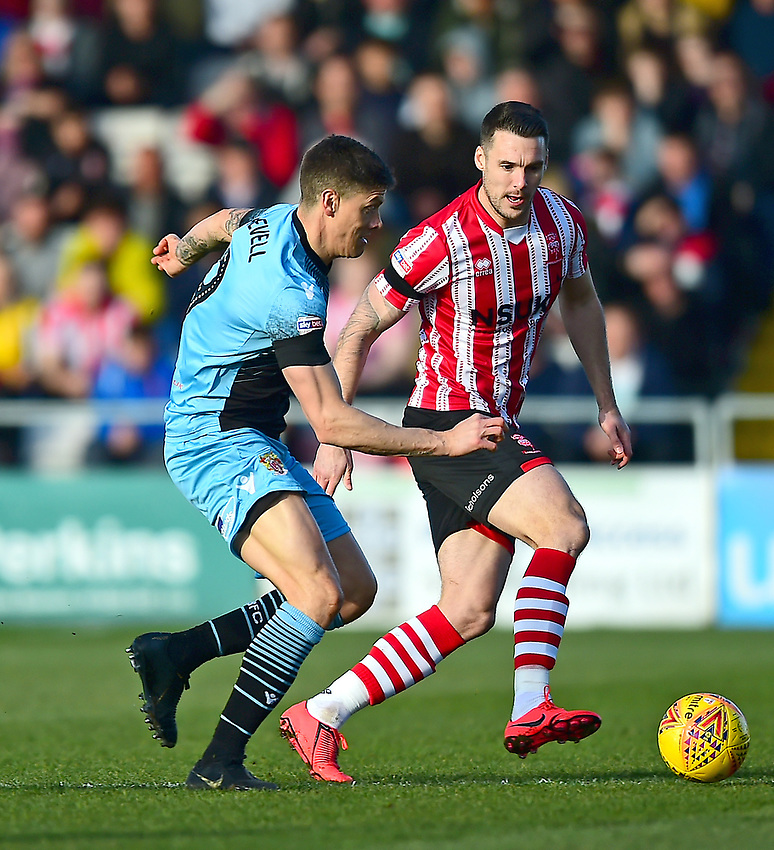 Lincoln City's Jason Shackell vies for possession with Stevenage's Alex Revell<br /> <br /> Photographer Andrew Vaughan/CameraSport<br /> <br /> The EFL Sky Bet League Two - Lincoln City v Stevenage - Saturday 16th February 2019 - Sincil Bank - Lincoln<br /> <br /> World Copyright © 2019 CameraSport. All rights reserved. 43 Linden Ave. Countesthorpe. Leicester. England. LE8 5PG - Tel: +44 (0) 116 277 4147 - admin@camerasport.com - www.camerasport.com