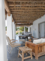 The large terrace is covered with a traditional roof comprised of wooden beams and dried palm fronds which offers shade to the outdoor seating area