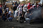 Palestinian protesters take cover during clashes with Israeli troops near the Jewish settlement of Bet El, near the West Bank city of Ramallah, October 29, 2015. Israeli security forces shot dead two Palestinian assailants in the occupied West Bank on Thursday, police and the army said, as a month-long spate of stabbing attacks showed no signs of abating. Photo by Shadi Hatem