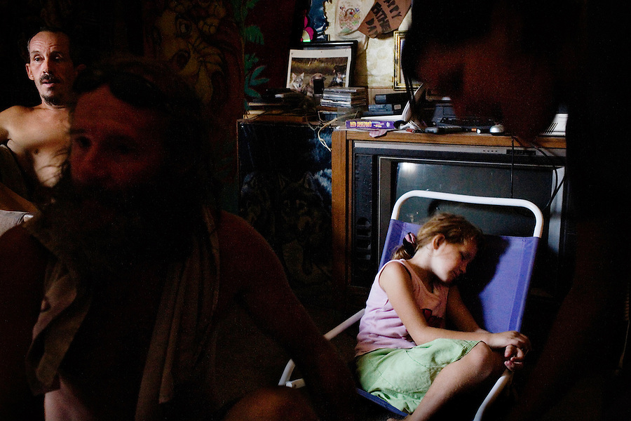 """Niland, California, July 26, 2008 - Ashley Appleby sleeps while her father Robert, far left, mother Crystal Strieker, right, and family friend, Ben Morofsky plan how to get the family out of their squatters' community. The Morofsky's had their three children taken from them by Child Protective Services three years ago. Ben says they took them because of their rough living conditions. CPS has been interviewing the family recently. They all fear CPS is planning on removing Ashley from the family. The Appleby's are trying to move to Washington State where there cousin owns land that they intend to build on. Ben says, """"She is our little princess, and we are going to do whatever we can to make sure they don't take her."""" ."""