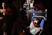 "Niland, California, July 26, 2008 - Ashley Appleby sleeps while her father Robert, far left, mother Crystal Strieker, right, and family friend, Ben Morofsky plan how to get the family out of their squatters' community. The Morofsky's had their three children taken from them by Child Protective Services three years ago. Ben says they took them because of their rough living conditions. CPS has been interviewing the family recently. They all fear CPS is planning on removing Ashley from the family. The Appleby's are trying to move to Washington State where there cousin owns land that they intend to build on. Ben says, ""She is our little princess, and we are going to do whatever we can to make sure they don't take her."" ."