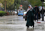 Palestinians walk during a rainy day in Gaza city on December 8, 2019. Photo by Ashraf Amra