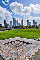 A vertical view with the top of the Police Memorial and the city skyline in the background at the park.