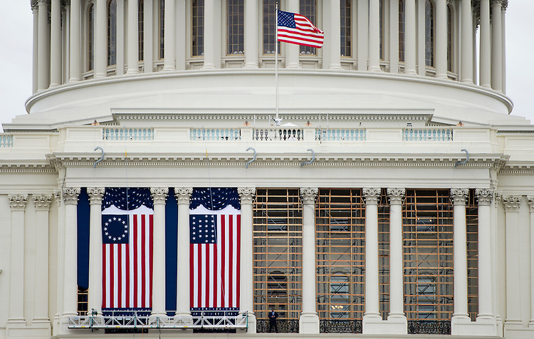 UNITED STATES - JANUARY 14: With a week to go, workers have begun hanging the flags on the west front of the Capitol on Monday, jan. 14, 2013, in preparation for President Barack Obama's inauguration.(Photo By Bill Clark)