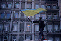 A protester waves an Ukrainian flag on top of a barricade under the snow during the protest against new draconian law to ban protestsacross the country.  Kiev. Ukraine
