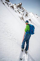 A skier stands next to a sad face drawing in the snow, playfully reacting disappointed in the snow conditions, which in this case are great, but very dangerous for avalanche. Kyrgyzstan.