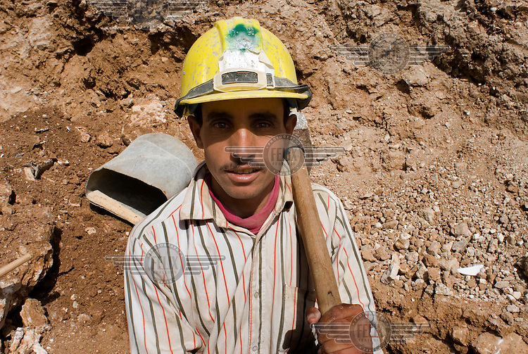 An Egyptian migrant worker holding a sledge hammer on a  construction site.