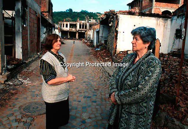 Two residents looking at the damage in the old town in Djakovica, Kosovo. The area was detroyed by repair by the Serbs in revenge for NATO bombings at Serb positions in May 1999. .Photo: Per-Anders Pettersson (ppettersso@aol.com)