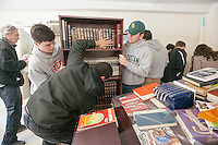 Volunteer teens from the predominantly Catholic Manhattan College, the Islamic Leadership School and Cong. Tehillah of Riverdale move prayer books prior to painting and cleaning the space of Beis Menachem synagogue located in the Masjid Al-Iman in the Parkchester neighborhood of the Bronx in New York on Sunday, April 21, 2013  The synagogue was given rent-free space in the mosque by the Iman, Sheik Moussa Drammeh, after losing its home due to the dwindling Jewish population in the area. The Sheik had previously received clothing and other donations from the synagogue and was returning their charity. (© Richard B. Levine)
