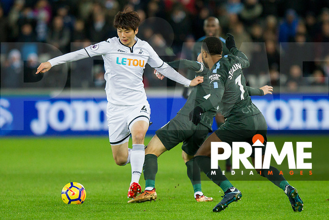 Ki Sung-Yueng of Swansea City takes on David Silva and Raheem Sterling of Manchester City during the EPL - Premier League match between Swansea City and Manchester City at the Liberty Stadium, Swansea, Wales on 13 December 2017. Photo by Mark  Hawkins / PRiME Media Images.