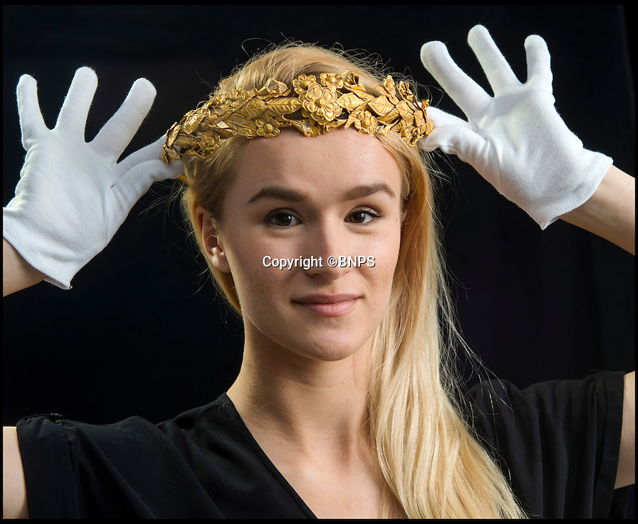 BNPS.co.uk (01202 558833)<br /> Pic: PhilYeomans/BNPS<br /> <br /> Maddi Puleston from Dukes carefully models the precious antiquity.<br /> <br /> Ancient Greek gold wreath discovered - In rural Somerset.<br /> <br /> An incredibly rare gold crown, believed to be more than 2,000 years old, has been discovered in the unlikely surroundings of a modest cottage in Somerset.<br /> <br /> The delicate solid gold myrtle wreath, which is thought to date from the time of Alexander the Great around 300BC, is expected to make at least a whopping £100,000 when it goes up for auction.<br /> <br /> The antiquity was retrieved from a tatty cardboard box kept under the owner's bed and he had no idea just how valuable it might be.<br /> <br /> The wreath will be sold by Duke's of Dorchester on June 9.
