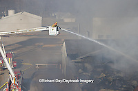 63818-02320 Firefighters extinguishing warehouse fire using aerial ladder truck viewed from top of ladder, Salem, IL
