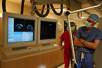 San Francisco, California, January 6, 2011 - From left, SurgiVision Clinical Engineering Manager Geoffrey Bates and University of California San Francisco chief resident Mark Richardson observe real time scans of patient Linda Sharpe during an iMRI surgery at University of California San Francisco Medical Center while. The MRI machine photographs the patient during the surgery allowing the doctors operating to view the procedure as well as support doctors and technicians to monitor from an outside room.  The iMRI procedure uses Deep brain stimulation (DBS), which has been used for over a decade to treat movement disorders such as Parkinson's disease, essential tremor, and dystonia. DBS uses a pulse generator implanted in the chest, similar to a pacemaker, to deliver pulses to specific regions of the brain via a permanently implanted electrode. In the U.S., DBS is normally done while the patient is awake, because the surgeon needs to induce the symptoms (like the involuntary movements of Parkinson's) to know if he's in the right place, and if the patient is unconscious, the symptoms can't be induced. Many patients find it hard to tolerate. Their head is clamped in a frame, they're aware of their surroundings, and the surgeon is deliberately producing tremors and twitches while they lie there...Interventional MRI (or iMRI) allows surgeons to implant these electrodes while the patient is unconscious taking advantage of MR imaging in real time by performing procedures inside the scanner itself. Doctors Paul Larson MD, and Philip Starr MD, PhD were both involved with this technology during its development in the 1990s. In 2002 they began to think about how to perform DBS using this technique at UCSF. Working with Alastair Martin PhD in the Department of Radiology, Jill Ostrem MD in the Department of Neurology, and others, they developed a technique of implantation using a modified but commercially available skull-mounted aiming device and custom-made, MR-compatible surgi