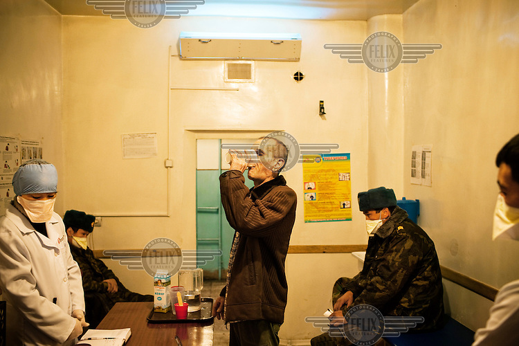 An inmate takes his oral tuberculosis (TB) treatment at SIZO 1, a pre-trial detention centre. All medical staff and guards wear masks as many of the detainees have MDR TB (multi-drug-resistant tuberculosis). Kyrgyzstan's prisons are experiencing a TB epidemic, where the incidence rate is estimated at 25 times higher than in civil society.