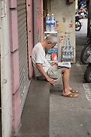 Hanoi<br /> , Vietnam - 2007 File Photo -<br /> <br /> An old vietnamese man smoke a cigarette while reading a newspaper outdoor in Hanoi ,  early morning; <br /> <br /> <br /> <br /> <br /> photo : James Wong-  Images Distribution