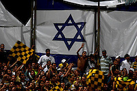 Beitar Jerusalem soccer fans holding yellow and black flags support their team during the final of the Israeli cup against Macabi Haifa, 2008 - 9 in the National Stadium of Ramat Gan in Tel Aviv. Beitar won the cup in a 3 - 0 result. Beitar Jerusalem FC was founded in the 1930's by the right-wing Revisionist Zionist movement, which later formed the Israeli Likud political party, during the British Mandate rule over Palestine. The chanting of the club is racist and mainly against Arabs. The team is the only one in the Israeli league to have never had an Arab player. Beitar is seen as the right wing and Mizrahi (Jews who came from Asia and Africa) club. Photo by Quique Kierszenbaum