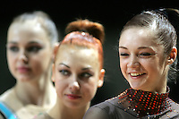 (R) Anna Bessonova of Ukraine (in focus) contemplates All-Around results during awards ceremony at 2006 Thiais Grand Prix in Paris, France on March 25, 2006. Background center and right are teammates Natalya Godunko and  Galina Shirkina of Ukraine.  (Photo by Tom Theobald)