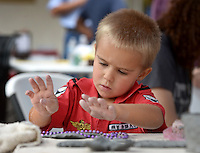 NWA Democrat-Gazette/BEN GOFF @NWABENGOFF<br /> Declan Markl (CQ), 4, of Rogers experiments using different objects to make impressions on clay on Sunday Aug. 23, 2015 during Sidewalk Sundays with Community Creative Center at the Walmart Museum in Bentonville. Community Creative Center, located in the Walton Arts Center's Nadine Baum Studios in Fayetteville, offers visual arts classes, workshops and camps for children and adults.