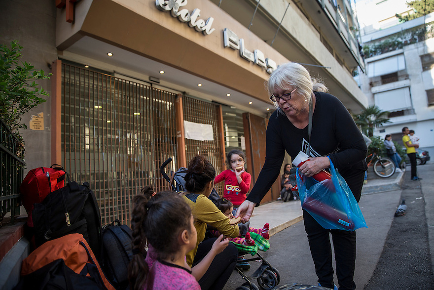 A volunteer hands out biscuits to children waiting outside the City Plaza Hotel, currently home to more than 300 people from Syria, Afghanistan, Iraq and Iran. Everyday more people come hoping to get a room at the hotel, but volunteers say they are at full capacity.