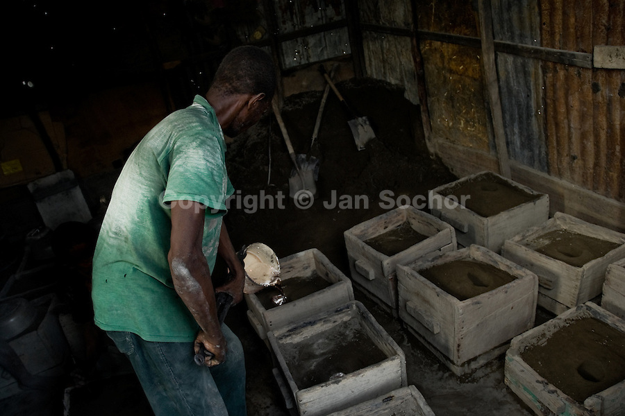 A Haitian man casting melted aluminium to make a kitchen pot in the aluminium recycling shop on the street of Port-au-Prince, Haiti, 11 July 2008.