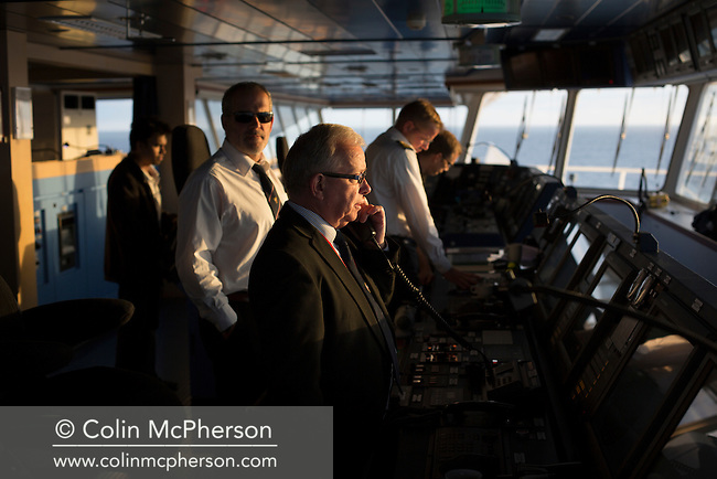 Dave Williamson (centre) of the Liverpool Pilotage Service on the bridge of an oil tanker off the coast of north Wales which he and his colleague Martin Baxter are piloting. The pilots navigated the tanker from Anglesey to the river Mersey, where it berthed at Tranmere Oil Terminal to discharge its cargo. The Liverpool Pilotage service celebrated its 250th anniversary in 2016.