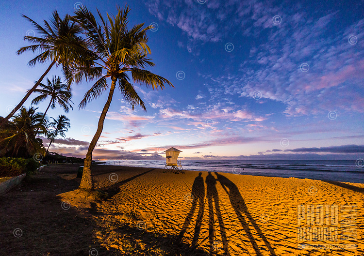 A photography team shoots the dawn breaking over White Plains Beach at Barbers Point, O'ahu.