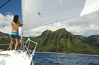 Asian local woman standing on bow of cruising sailboat as it approaches Kauai's north shore