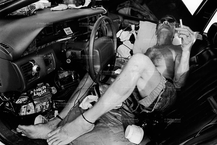 USA. Louisiana. New Orleans. Orleans Parish. Aftermath of hurricane Katrina. Lenny Trollman is a homeless who lives in his car. He lays on the front seat and smokes a cigarette. He has refused to leave the town and stayed during and after the storm even if the area is empty and most of its inhabitants have left the city.  © 2005 Didier Ruef