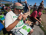 A festival goer rolls a joint at Hempfest 2014 on the Seattle on August 17, 2014.  Seattle Hempfest, celebrating its 23rd anniversary, features six stages of music, world renowned speakers, hundreds of food, arts, crafts and political booths.   ©2014.  Jim Bryant Photo. All rights reserved.