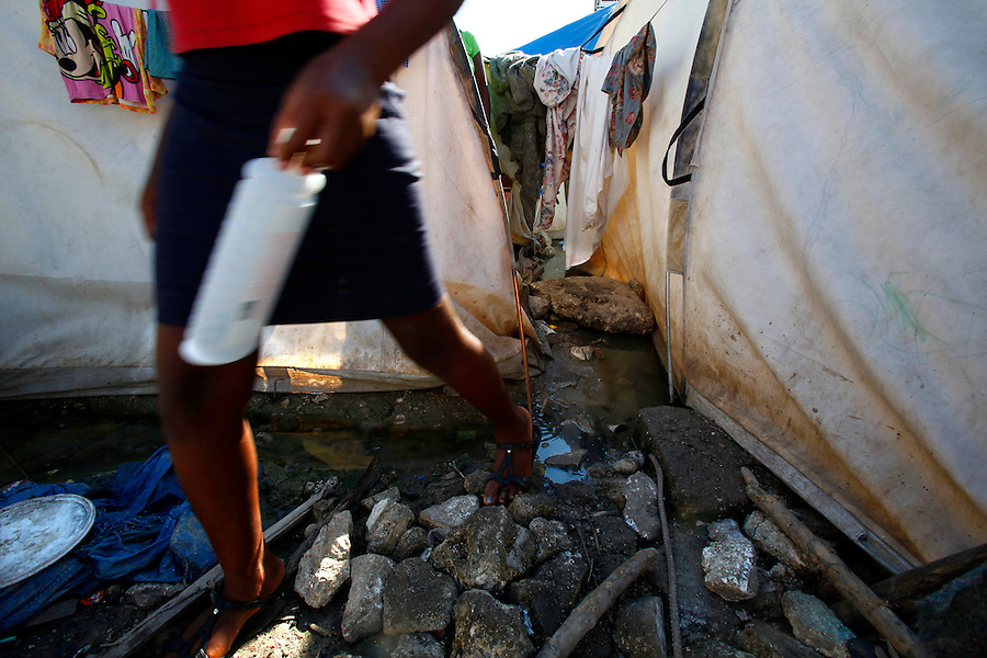 Nov 11, 2010 - Port-au-Prince, Haiti.A resident of a tent city in Port-au-Prince, Haiti steps over stagnant water left behind by Hurricane Tomas that is filled with garbage and possible human waste as she carries a bottle of shampoo to the makeshift showers on Thursday, November 11, 2010 as fears of a Cholera outbreak spread through the area just days after cases of the infection were confirmed in Haiti's capital. Officials from the Pan American Health Organization warn that Haiti's cholera epidemic, spread primarily through consuming infected water and food, is likely to grow much larger in the wake of Hurricane Tomas.  (Credit Image: Brian Blanco/ZUMA Press)