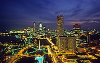 Singapore. Raffles City, the War Memorial and the Medan in the foreground, container terminal in the background. Evening.