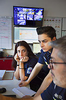 Switzerland. Canton Ticino. Pregassona. Control room  at Croce Verde Lugano's headquarters. The emergency doctor Daniele Speciale (R) explains to two paramedics how to read electrocardiogram's curves. They all work for the Croce Verde Lugano and wear blue uniforms. The woman (C) is a professional certified nurse, the other woman (L) is a volunteer specifically trained in emergency rescue. The Croce Verde Lugano is a private organization which ensure health safety by addressing different emergencies services and rescue services. Volunteering is generally considered an altruistic activity where an individual provides services for no financial or social gain to benefit another person, group or organization. Volunteering is also renowned for skill development and is often intended to promote goodness or to improve human quality of life. Pregassona is a quarter of the city of Lugano.13.01.2018 © 2018 Didier Ruef