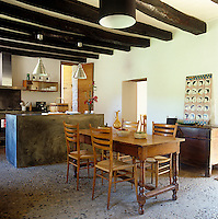 The kitchen/diner is a combination of contemporary and rustic with a concrete island and a farmhouse table
