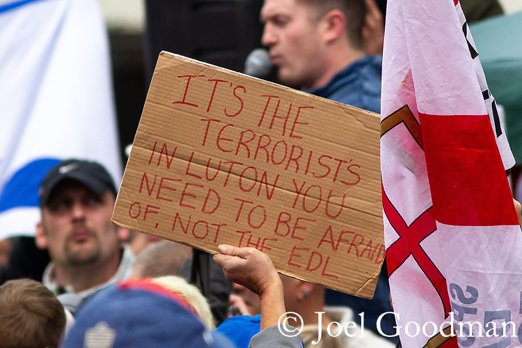 """© Joel Goodman - 07973 332324 . 05/05/2012 .  Luton , UK . A protester lifts a home made placard reading """" It's the terrorists in Luton you need to be afraid of, not the EDL """" . Approximately 1,500 people take part in an EDL ( English Defence League ) march in Luton , understood to have been policed by over 1,000 officers . Photo credit: Joel Goodman"""