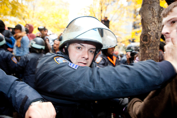 """After a slight altercation with a protester the NYPD responds with a heavy hand in Zuccotti Park on November 17, 2011 in New York City.  After subduing the perpetrator, who wound up bleeding profusely from his head, the police were jeered by hundreds of protesters with the chant, """"Get out of our park!"""""""