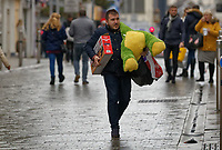 A man carries gifts as he joins other last minute Christmas shoppers in Oxford Street, in the city centre of Swansea, Wales, UK. Sunday 24 December 2017