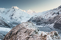 Soft pastel dawn over Tasman Glacier as seen from Ball Ridge with De la Beche 2950m in background and climber giving sense of scale at end of ridge, Mt. Cook National Park, World Heritage, Mackenzie Country, South Island, New Zealand