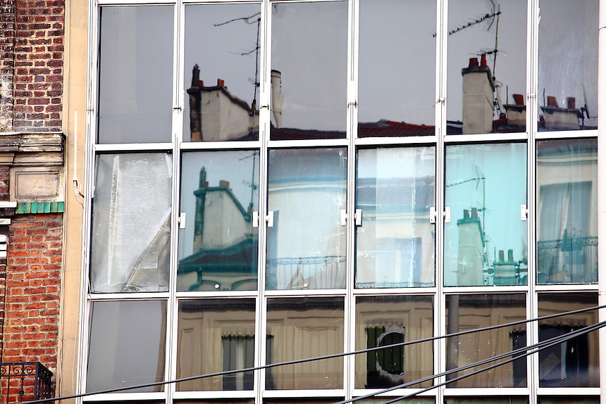 Sorting from Paris in the direction of Kremlin- Bicêtre, near the Périférique, the glass wall of an old building to be renovated reflects the smokestacks and the windows of the opposite one, in a picturesque view. Digitally Improved Photo.