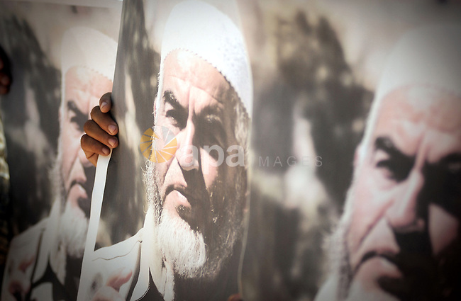 Palestinian Hamas supporters carry pictures of Sheikh Raed Salah during anti-Israeli protest at the port of Gaza City on May 31, 2010. At least 10 activists were killed in an Israeli naval takeover on Monday of a Gaza-bound aid convoy, an Israeli military spokesman said. Photo by Mostafa Hassona
