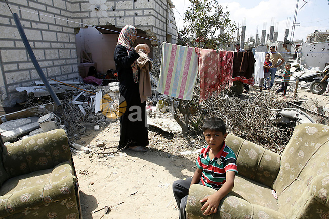 "A Palestinian woman works as her son plays at their destroyed house in Khan Yunis in the southern Gaza Strip on September 11, 2014. Israel's deputy foreign minister,Tzahi Hanegbi , warned that Hamas was likely to resume ""violence"" if it feels it has made no political gains from upcoming talks in Cairo. Photo by Abed Rahim Khatib"