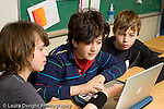 Public Middle School Grade 7 male students working together using laptop horizontal
