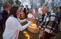 NWA Democrat-Gazette/BEN GOFF @NWABENGOFF<br /> Carolyn Cole (right) of Rogers passes the challah bread to  Sarah Lennick of Allentown, Pa. on Friday April 8, 2016 as members of the congregation have s'mores and snacks around a fire following the inaugural service at the Community Synagogue of Northwest Arkansas in Lowell.