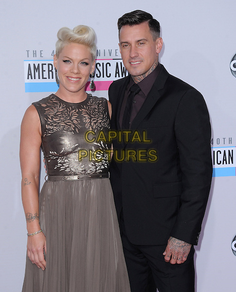 Pink (Alecia Moore) & Carey Hart.40th Anniversary American Music Awards - Arrivals held at Nokia Theatre L.A. Live, Los Angeles, California, USA..November 18th, 2012.AMA AMAs half  length brown beige gold sleeveless dress perforated cut out away black suit married husband wife piink pinnk  .CAP/DVS.©DVS/Capital Pictures.